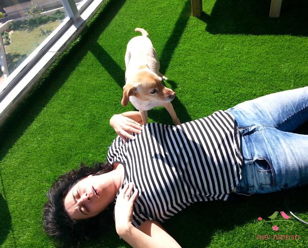 מיכל שלוין מתענגת על הדשא הסינטטי במרפסת שלה